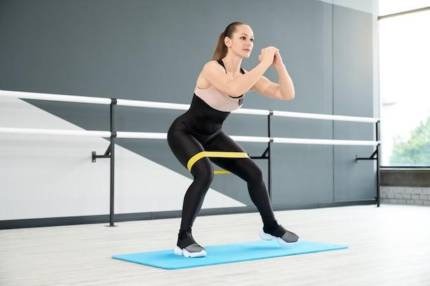Muskulöse frau, die beine mit fitnessband trainiert