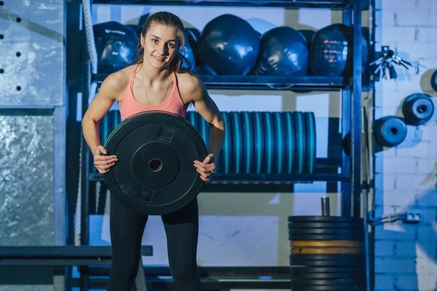 Muskulöse frau, die crossfit training an der turnhalle tut. crossfit frau. crossfit-stil.