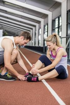 Muskulöse frau, die eine knöchelverletzung in crossfit turnhalle hat