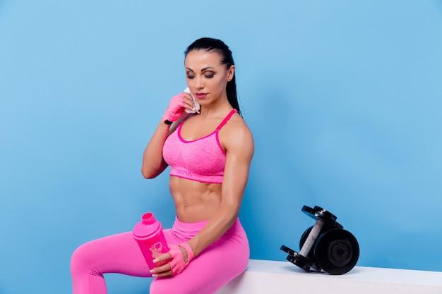 Muskulöse frau, die eine pause hat und flasche hält