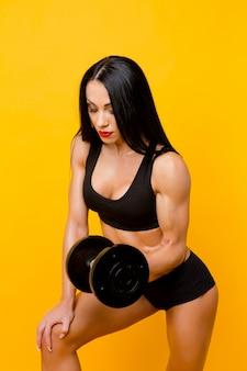 Muskulöse frau, die hanteln hält