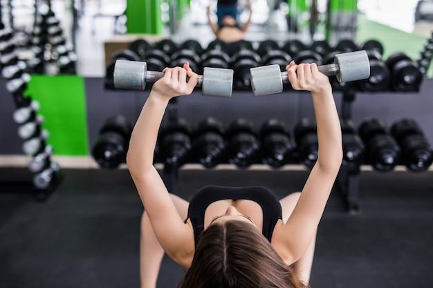 Muskulöse frau, die im fitnesscenter mit zwei hanteln ausarbeitet
