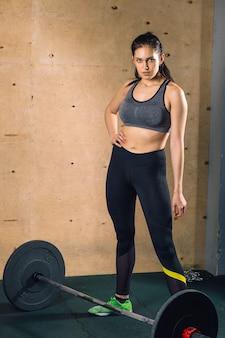 Muskulöse frau in einem fitnessstudio, das schwere gewichtsübungen macht