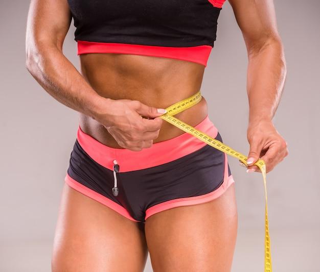 Muskulöse frau misst taille des perfekten körpers.