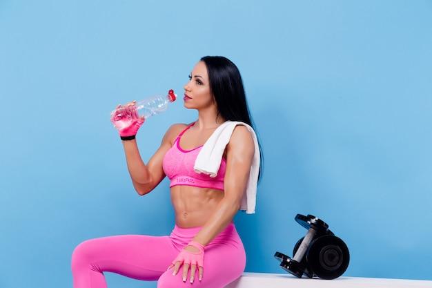 Muskulöse frau ruhen sich aus und trinken wasser
