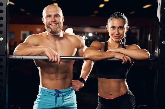 Muskulöse frau und ihr starker freund, die sich auf fitnessgeräte stützen, während sie in die kamera schauen