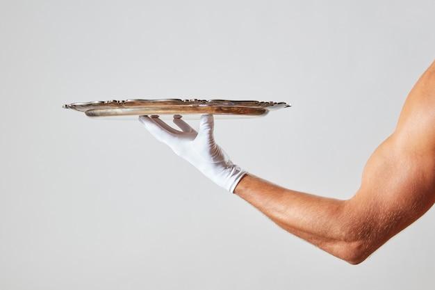Muskulöse hand des kellners in einem weißen handschuh, der ein silbernes vintage leeres tablett hält