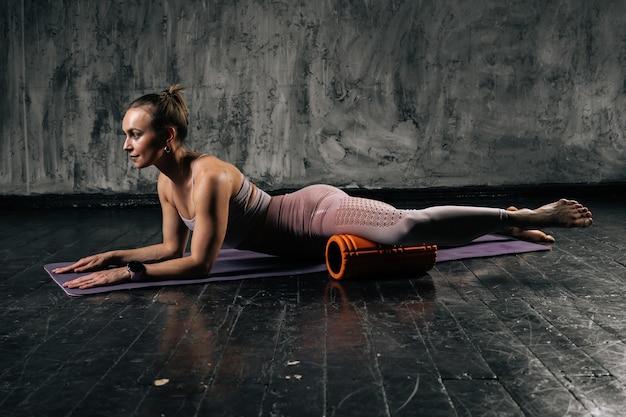 Muskulöse junge athletische frau, die fußmuskeln mit schaumrollenmassagegerät massiert, das auf yogamatte liegt.