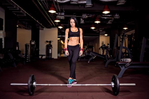 Muskulöse junge eignungsfrau, die für schwere kreuzhebenübung sich vorbereitet