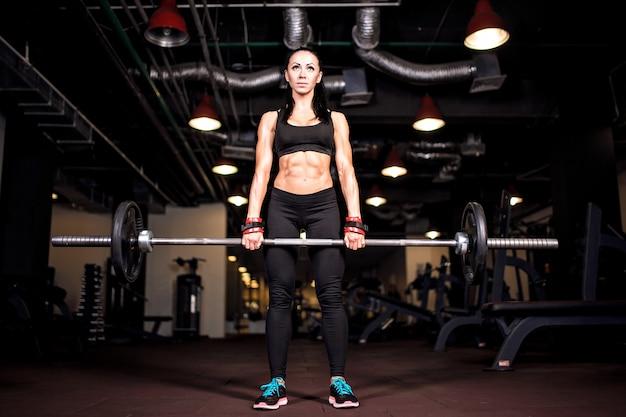 Muskulöse junge fitnessfrau, die schwere kreuzhebenübung im fitnessstudio tut