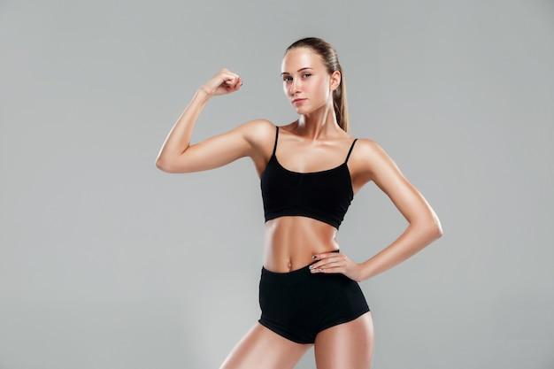 Muskulöse junge sportlerin auf grau
