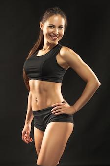 Muskulöse junge sportlerin auf schwarzem