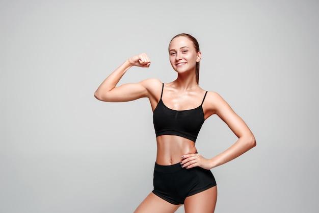 Muskulöse junge sportlerin, die auf grau aufwirft