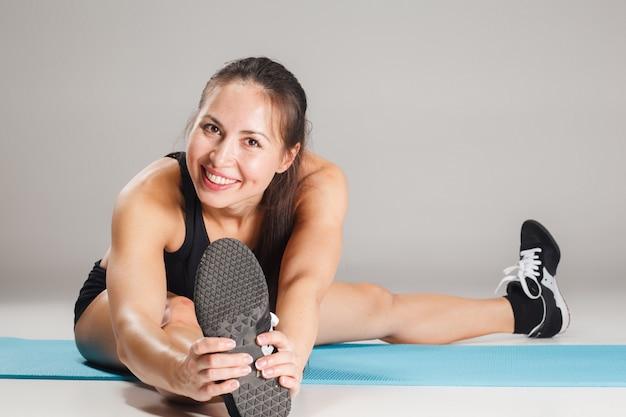 Muskulöse junge sportlerin, die auf grau ausdehnt