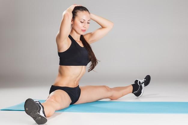 Muskulöse junge sportlerin, die auf grau streckt