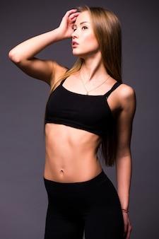 Muskulöse junge sportlerin, die auf grauer wand steht
