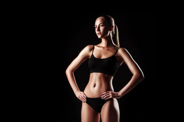 Muskulöse junge sportlerin, die auf schwarz aufwirft