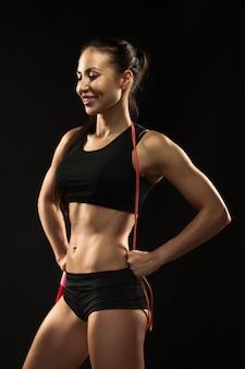 Muskulöse junge sportlerin mit einem springseil auf schwarz
