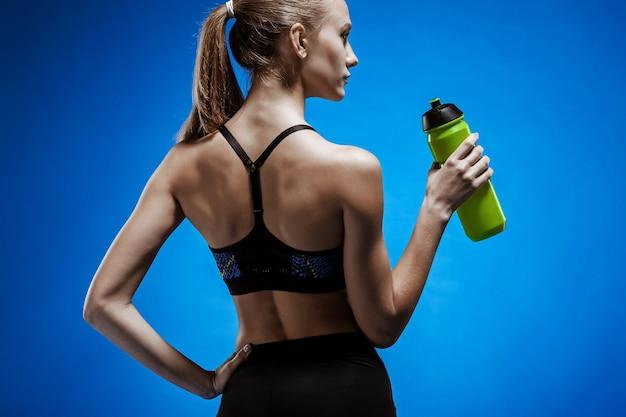 Muskulöse junge sportlerin mit einem wasser auf blau