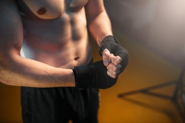 Muskulöse männliche person hände in schwarzen bandagen