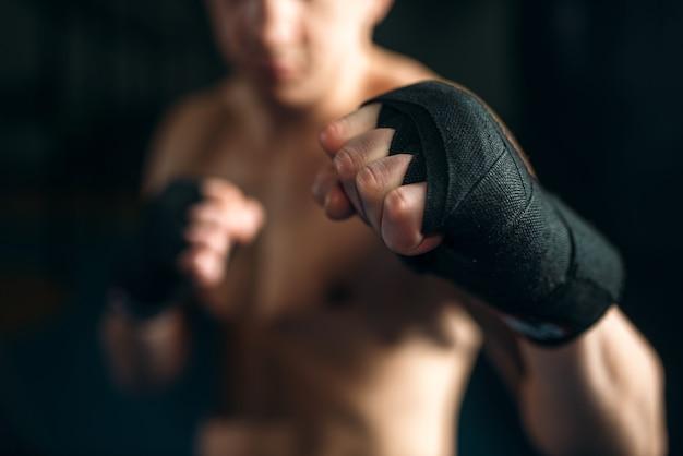Muskulöse männliche person in schwarzen bandagen