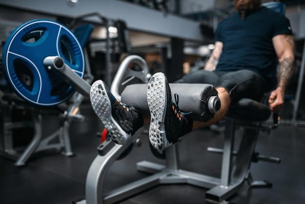 Muskulöse männliche person trainiert beine auf übungsmaschine, training im fitnessstudio.