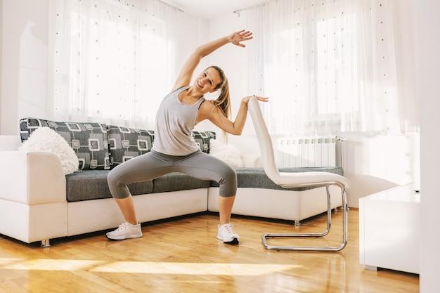 Muskulöse sportlerin in form, die fitnessübungen für ihren rücken macht, während sie sich auf stuhl stützt