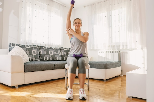 Muskulöse sportlerin in form, die zu hause auf dem stuhl sitzt, hantel hebt und mit der anderen hand bizeps zeigt.
