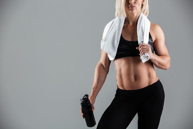 Muskulöse sportlerin mit einem handtuch