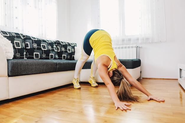 Muskulöse starke sportlerin, die zu hause dehnübungen auf dem boden macht
