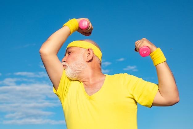 Muskulöser älterer sportmann im gesundheitswesen fröhlicher lebensstil älterer mann im fitnessstudio, der mit gewichten trainiert ...