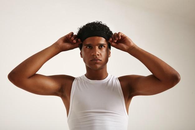 Muskulöser afroamerikanischer athlet im weißen basketballhemd, der sein schwarzes stirnband anpasst und leicht schaut