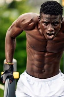 Muskulöser afroamerikanischer athlet mit nacktem, geformtem oberkörper, der liegestütze am stufenbarren in der stadtlandschaft macht, front shot