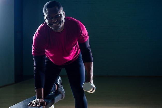 Muskulöser afroamerikanischer mann, der liegestütze mit hanteln im fitnessstudio auf schwarzem hintergrund macht