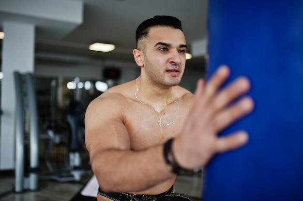 Muskulöser arabischer mann, der im modernen fitnessstudio trainiert. fitness arabische männer mit nacktem oberkörper machen übungen mit boxsack.