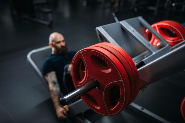 Muskulöser athlet auf übungsmaschine mit langhantel, training im fitnessstudio.