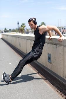 Muskulöser athlet, der draußen arbeitet, seinen körper ausdehnend