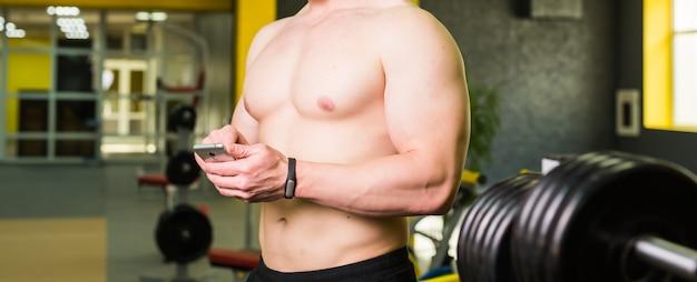 Muskulöser athlet, der trainingsprogramm auf smartphone-anwendung nach perfektem crossfit im fitnessstudio überprüft