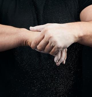 Muskulöser athlet in schwarzer uniform reibt sich die hände mit weißer trockener sportmagnesia, pulver streut