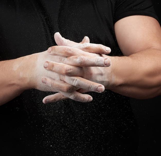 Muskulöser athlet in schwarzer uniform reibt sich die hände mit weißer trockener sportmagnesia