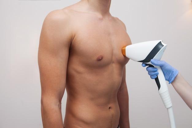 Muskulöser athletenmann mit glatter klarer haut. epilation und haarentfernung im schönheitssalon. männliches laser-haarabbaukonzept. kosmetikerin mit modernen geräten für verfahren. haut- und schönheitspflege