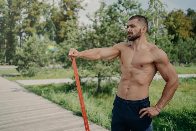 Muskulöser athletischer mann hat training mit elastischem widerstandsband posiert mit hemdlosem muskulösem körper, steht draußen, konzentriert in der ferne. sportler sportler hat training im park. gesunder lebensstil