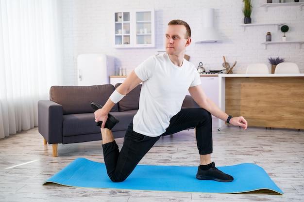 Muskulöser athletischer mann in einem t-shirt, der zu hause aufwärmübungen macht. während der quarantänezeit zu hause sport treiben. fitness außerhalb des fitnessstudios