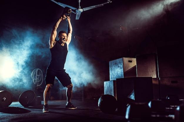 Muskulöser attraktiver kaukasischer bärtiger mann, der zwei kettlebells in einer turnhalle anhebt. hantelscheiben, hantel und reifen im hintergrund.