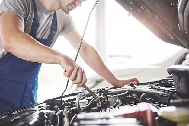Muskulöser autoservice-arbeiter, der fahrzeug repariert.