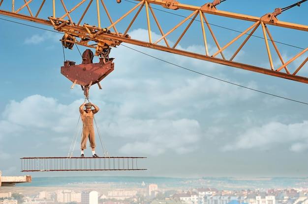 Muskulöser baumeister mit nacktem oberkörper, der hoch auf eisenkonstruktion steht und an seilen hält. mann mit hut und arbeitskleidung, der in die kamera schaut. blauer himmel mit wolken im hintergrund.