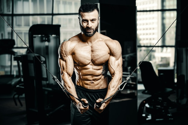 Muskulöser bodybuilder bei cable crossovers fitness