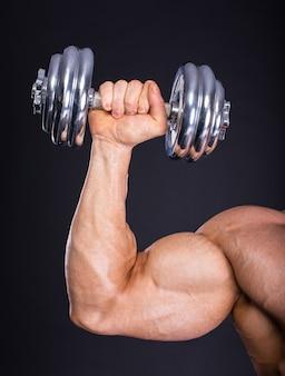 Muskulöser bodybuilder, der übung mit gewicht tut.