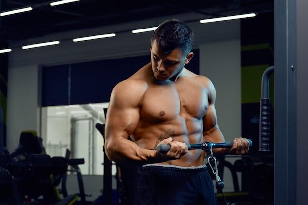 Muskulöser bodybuilder, der übungen auf kabelkreuzungsmaschine in der turnhalle tut starker athletischer mann zeigt körper, bauchmuskeln, bizeps und trizeps heraus arbeiten, das gewicht zunehmen und oben muskeln pumpen.