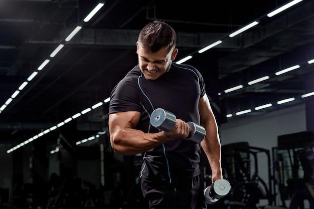 Muskulöser bodybuilder, der übungen mit dummkopf in der turnhalle tut starker athletischer mann zeigt körper, bauchmuskeln, bizeps und trizeps heraus arbeiten, das gewicht gewinnen und oben muskeln mit dummköpfen pumpen.